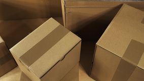 Pan over brown carton box parcels stacked on wooden office desk ready for shipment or just delivered. Pan with elevated view from top over brown carton box stock video footage