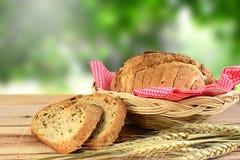 Pan en cesta y trigo en la tabla de madera Fotografía de archivo libre de regalías