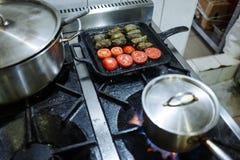 Pan en een vierkante pan met dolma en tomaten op een gasoven in de keuken van het restaurant royalty-vrije stock foto's