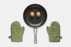 Pan en groene handschoen en eieren op witte achtergrond Stock Foto