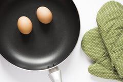 Pan en groene handschoen en eieren op witte achtergrond Stock Foto's