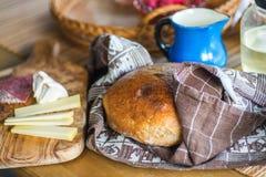Pan en toalla, jarra azul, salami y queso Fotografía de archivo