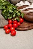 Pan en un tablero de madera con los tomates Imagen de archivo