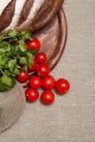Pan en un tablero de madera con los tomates Fotografía de archivo libre de regalías