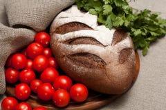 Pan en un tablero de madera con los tomates Imagen de archivo libre de regalías
