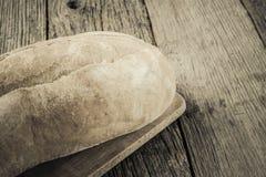 Pan en un tablero de pan con madera rústica Foto de archivo