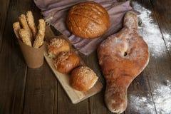 Pan en una tabla rústica de madera, bollos del pan en un tablero de madera y las barras de pan con las semillas de sésamo con el  fotos de archivo