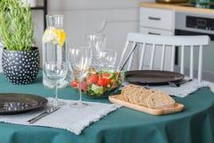 Pan, ensalada, placa y copas de vino en la tabla cubierta con el mantel verde esmeralda foto de archivo