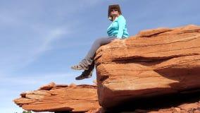 Pan erreichen herauf den kaukasischen Frauentouristen einen tiefstand, der auf einem Steinfelsen im Grand Canyon sitzt stock video footage