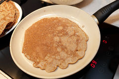 Pan with flaxseed meal pancake on a stove. At home royalty free stock photo
