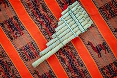 Pan flute on traditional andean fabric background. South America royalty free stock photos