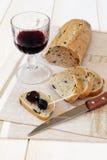 Pan francés con las aceitunas, las aceitunas de Provencal y un vidrio de los wi rojos Fotografía de archivo
