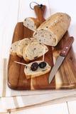 Pan francés con las aceitunas y las aceitunas de Provencal en una tabla de cortar Foto de archivo
