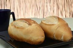 Pan francés, en la placa con la taza negra en fondo fotos de archivo