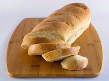 Pan francés en la tabla de cortar de madera Fotos de archivo