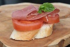 Pan francés rematado con el tomate y el jamón Fotos de archivo