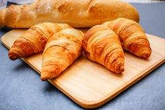 Pan francés y cuatro cruasanes en una tabla de cortar de madera en el papel oscuro del arte foto de archivo