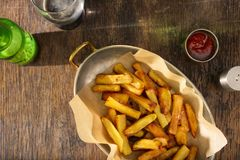Pan of French fries with ketchup and dark beer Stock Photos