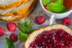 Pan fresco con el atasco de frambuesa Desayuno con las bayas y la menta Imagen de archivo libre de regalías