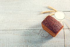 Pan fresco con leche y espiguillas del trigo en tableros de madera Fotografía de archivo
