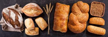 Pan fresco con los oídos del trigo en la tabla oscura, visión superior Imágenes de archivo libres de regalías
