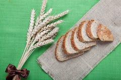 Pan fresco con los oídos del trigo en una lona. Fotos de archivo
