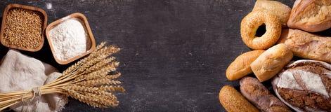 Pan fresco con los oídos del trigo y el cuenco de harina, visión superior Foto de archivo libre de regalías