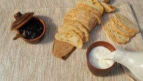 Pan fresco del desayuno sabroso con el atasco y la leche La leche se vierte en una taza Tostada con el atasco de la fruta en serv metrajes