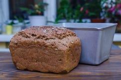 Pan fresco del pan negro hecho en casa con la forma del pan en superficie de madera Imágenes de archivo libres de regalías