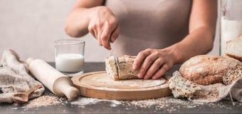 Pan fresco en primer de las manos en viejo fondo de madera Fotografía de archivo libre de regalías