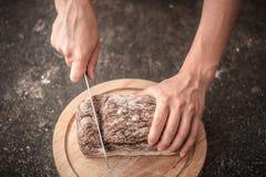 Pan fresco en primer de las manos en viejo fondo de madera Foto de archivo