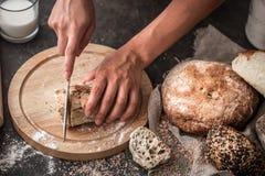 Pan fresco en primer de las manos en viejo fondo de madera Fotos de archivo