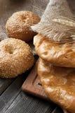 Pan fresco y rollos con los oídos del trigo en la tabla de madera Fotografía de archivo libre de regalías