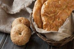 Pan fresco y rollos con los oídos del trigo en la tabla de madera Imagenes de archivo