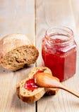 Pan fresco y tarro con la mermelada de fresa hecha en casa en la tabla de madera rústica fotografía de archivo