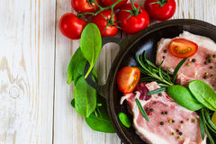 Pan of Fresh raw pork meat with pepper. Lime, rosemary and spinach. Marinade. Ready ror cooking Royalty Free Stock Image