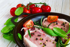 Pan of Fresh raw pork meat with pepper. Lime, rosemary and spinach. Marinade. Ready ror cooking Stock Images