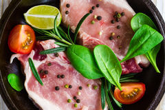 Pan of Fresh raw pork meat with pepper. Lime, rosemary and spinach. Marinade. Ready ror cooking Royalty Free Stock Photos