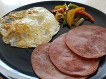 Pan fried back bacon, over easy egg, and sauteed bell pepper breakfast. On a blue plate closeup stock images