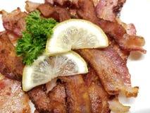 Pan Fried Bacon Strips friável com limão fotografia de stock royalty free