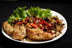Pan fried chicken with roasted vegetables Stock Photos