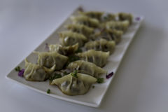 Pan Fried Chinese Dumplings on Plate 2. A plate of delicious pan fried Chinese dumplings decorated with shallots and purple flowers royalty free stock photos