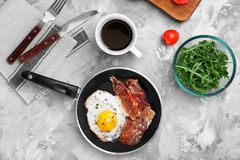 Pan with fried egg and bacon. On table royalty free stock images