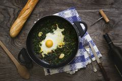 Pan with fried egg and spinaches Royalty Free Stock Images