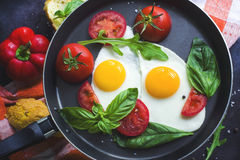 Pan of fried eggs, basil and tomatoes with bread on grunge metallic table surface. Royalty Free Stock Photography