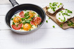 Pan of fried eggs with tomatoes, cheese, spring onion, herbs on a white table. Bread with spread. White wooden table. Concept of f Stock Image