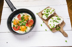 Pan of fried eggs with tomatoes, cheese, spring onion, herbs on a white table. Bread with spread. White wooden table. Concept of f Royalty Free Stock Image