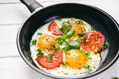 Pan of fried eggs with tomatoes, cheese, spring onion, herbs on a white table. White wooden table. Concept of food. Breakfast time.  Royalty Free Stock Image