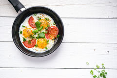 Pan of fried eggs with tomatoes, cheese, spring onion, herbs on a white table. White wooden table. Concept of food. Breakfast time Royalty Free Stock Images