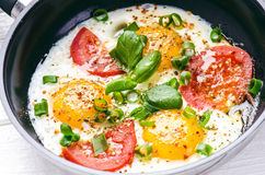 Pan of fried eggs with tomatoes, cheese, spring onion, herbs on a white table. White wooden table. Concept of food. Breakfast time Royalty Free Stock Image